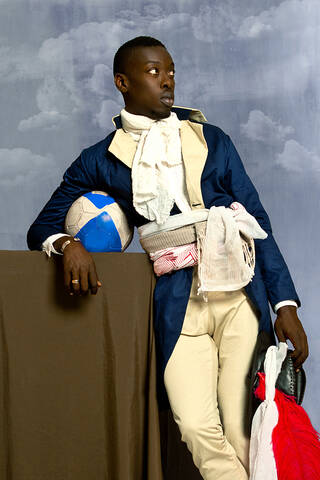Portrait of a Senegalese man in 18th-century uniform looking away from the viewer in a relaxed pose.