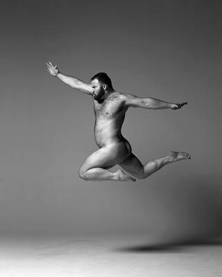 Nude man leaping in mid-air